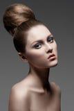 Femme avec le renivellement et la coiffure photographie stock