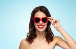 Femme avec le rouge à lèvres rouge et les nuances en forme de coeur Image stock