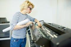 Femme avec le rouleau de papier vérifiant l'imprimante image stock