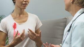 Femme avec le ruban rose au contrôle de docteur, conscience de cancer du sein, prévention clips vidéos