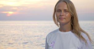 Femme avec le ruban rose de conscience par la mer banque de vidéos