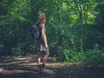 Femme avec le sac à dos dans la forêt Photographie stock libre de droits