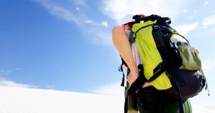 Femme avec le sac à dos marchant dans le désert 4k clips vidéos