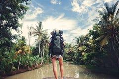 Femme avec le sac à dos se tenant près de la grande rivière tropicale et regardant loin Photos libres de droits