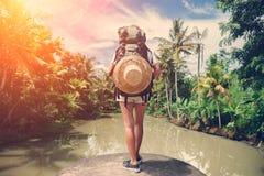 Femme avec le sac à dos se tenant sur le bord près de la grande rivière tropicale Photo libre de droits