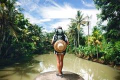 Femme avec le sac à dos se tenant sur le bord près de la grande rivière tropicale et regardant loin Image libre de droits