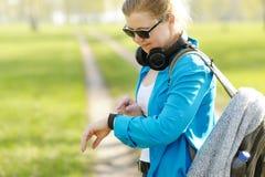 Femme avec le sac à dos sur les utilisations d'épaules des montres intelligentes Images libres de droits