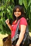 Femme avec le sac de main en cuir avec l'arbre derrière Photographie stock