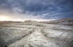 Femme avec le sac à dos dans les montagnes de désert Photos stock