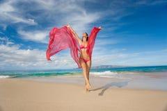 femme avec le sarong rose sur la plage tropicale Photos stock