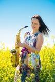 Femme avec le saxophone dans le domaine de graine de colza Images libres de droits