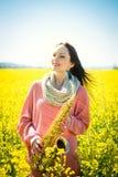 Femme avec le saxophone dans le domaine de graine de colza Photos stock