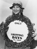 Femme avec le signe avec le nombre des jours d'achats jusqu'à ce que Noël (toutes les personnes représentées ne sont pas plus lon Image libre de droits
