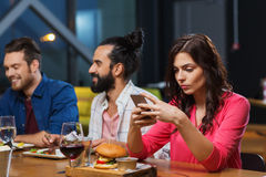 Femme avec le smartphone et les amis au restaurant Image stock