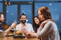 Femme avec le smartphone et les amis au restaurant Photographie stock