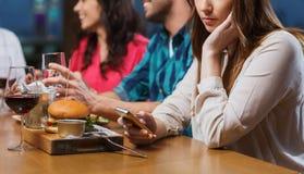 Femme avec le smartphone et les amis au restaurant Photo stock