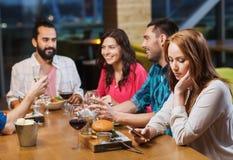Femme avec le smartphone et les amis au restaurant Images libres de droits