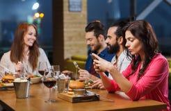 Femme avec le smartphone et les amis au restaurant Photo libre de droits