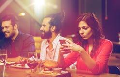 Femme avec le smartphone et les amis au restaurant Photos stock