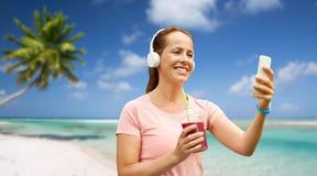 Femme avec le smartphone et secousse écoutant la musique image libre de droits