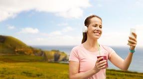 Femme avec le smartphone et secousse écoutant la musique photo libre de droits