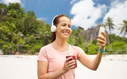 Femme avec le smartphone et secousse écoutant la musique photographie stock