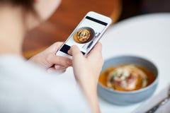 Femme avec le smartphone photographiant la nourriture au café Photographie stock libre de droits