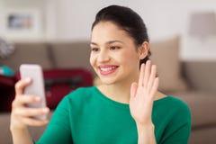 Femme avec le smartphone prenant l'appel de selfie ou de vidéo Photo stock