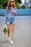 Femme avec le smoothie et la laitue dans leurs mains sur une rue de ville Photos stock