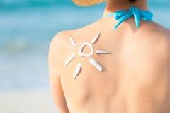 Femme avec le soleil tiré de la protection solaire dessus de retour Images libres de droits