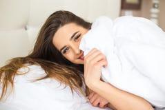 Femme avec le sourire de beauté se trouvant sur un lit blanc dans la maison Photos libres de droits