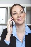 Femme avec le téléphone au bureau Photo stock