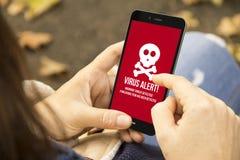 Femme avec le téléphone d'alerte de virus en parc Photographie stock