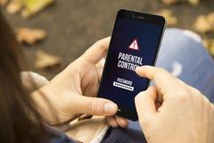 Femme avec le téléphone de contrôle parental en parc Image libre de droits