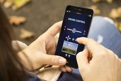 femme avec le téléphone du contrôle APP de bourdon en parc Image libre de droits