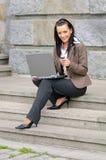 Femme avec le téléphone et l'ordinateur portatif Photographie stock