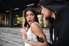 Femme avec le téléphone portable criant et attaquée par l'homme criminel Images stock
