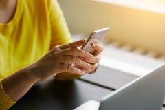 Femme avec le téléphone portable et l'ordinateur portatif photographie stock