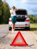 Femme avec le téléphone près de la voiture cassée Photo stock
