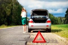 Femme avec le téléphone près de la voiture cassée Image stock