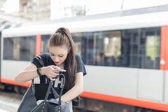 Femme avec le téléphone regardant dans la sa bourse avec la hâte Images libres de droits