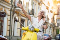 Femme avec le téléphone sur le scooter photos libres de droits