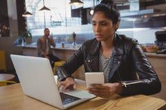 Femme avec le téléphone utilisant l'ordinateur portable en café Photos stock