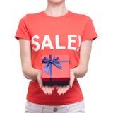 Femme avec le T-shirt avec une remise disponible d'achat de boutique de boîte de vente d'inscription Photo libre de droits