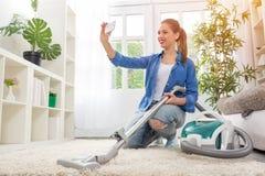 Femme avec le tapis de nettoyage d'aspirateur et le selfie de prise Photographie stock libre de droits