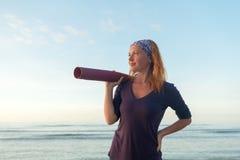 Femme avec le tapis de yoga Image libre de droits