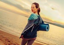 Femme avec le tapis de yoga se tenant sur la plage Photo stock