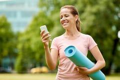 Femme avec le tapis et le smartphone d'exercice au parc photo stock