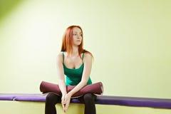 Femme avec le tapis sur des genoux Photo stock