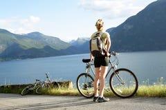 Femme avec le vélo au-dessus du fjord photo stock